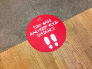 floor with a social distancing sign in red and white says stay safe