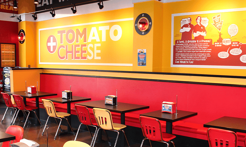 chairs at tables and a large wall sign tom + chee