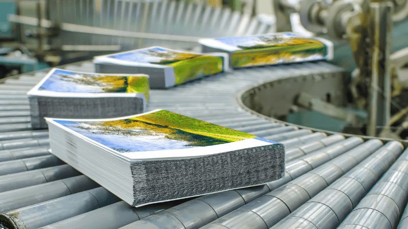 books on a rolling conveyer rack at a printer